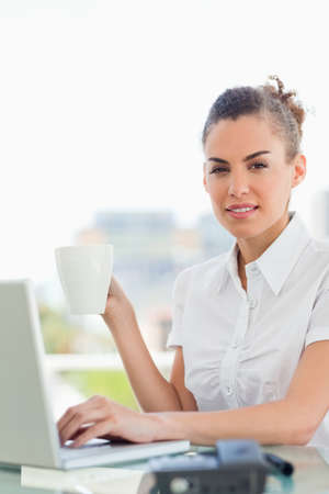 frizzy: Portrait of a frizzy haired woman with a coffee while tapping on her laptop in a bright office LANG_EVOIMAGES