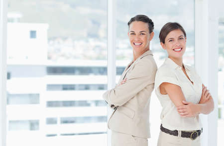 backs: Two smiling businesswomen with their backs to one another as they smile.