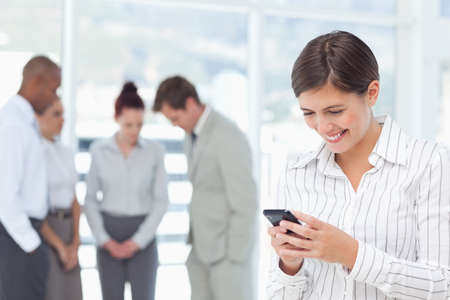 telephone saleswoman: Smiling young saleswoman with cellphone and colleagues behind her