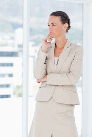 saleswoman: Thoughtful saleswoman standing next to window