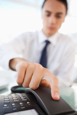 hangup: Close-up of a man picking up a landline phone in a bright office LANG_EVOIMAGES