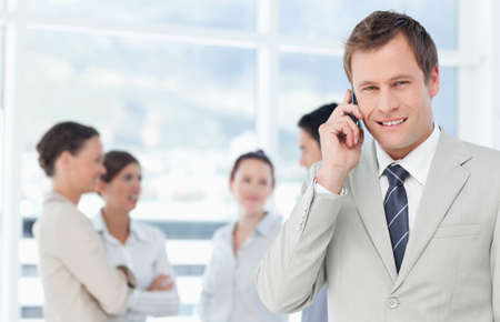 telephone saleswoman: Smiling young salesman on his cellphone with colleagues behind him LANG_EVOIMAGES