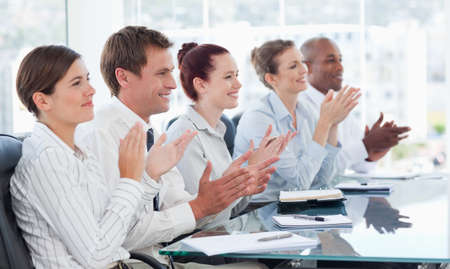 tradespeople: Side view of applauding young tradespeople sitting at a table