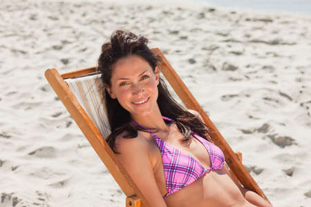 pink bikini: Portrait of a woman in pink bikini sitting in a deck chair on the beach LANG_EVOIMAGES