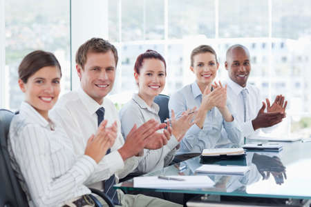 applauding: Side view of applauding young salesteam sitting at a table