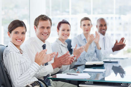 salespeople: Side view of applauding young salespeople sitting at a table