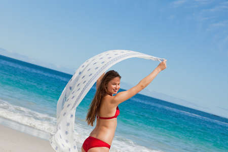 sarong: Close-up of a beautiful woman playing with a sarong with the sea in background LANG_EVOIMAGES
