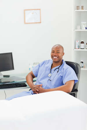 examination room: Smiling male doctor in scrubs sitting in his examination room