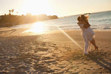 enamorados besandose: Puesta del sol con los amantes que se besan en la playa LANG_EVOIMAGES