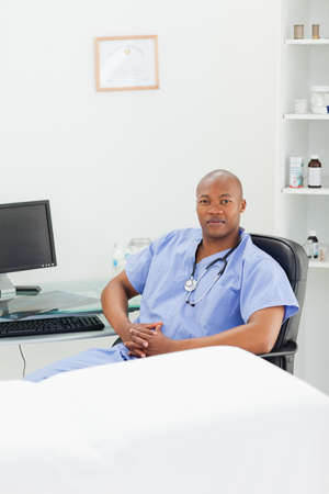 examination room: Male doctor in scrubs sitting in his examination room