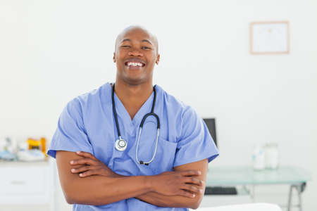 examination room: Smiling male doctor in scrubs with arms folded in his examination room LANG_EVOIMAGES