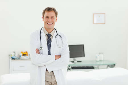 examination room: Smiling male doctor with his arms folded in his examination room LANG_EVOIMAGES
