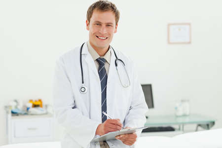 examination room: Smiling male doctor with clipboard and pen standing in his examination room