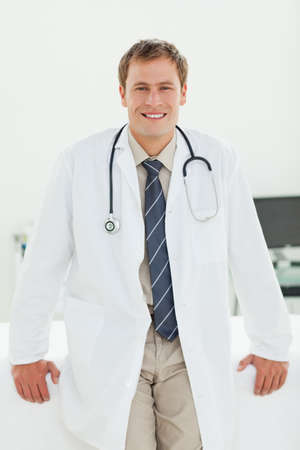 examination room: Smiling male doctor standing in his examination room