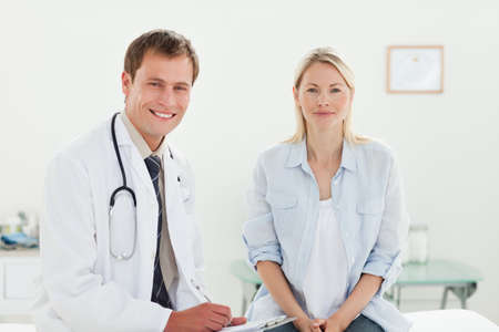 examination room: Smiling male doctor with his patient sitting in examination room LANG_EVOIMAGES