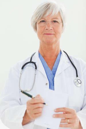 prescription pad: Mature doctor pointing at prescription pad