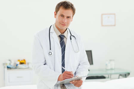examination room: Smiling male doctor with clipboard standing in examination room