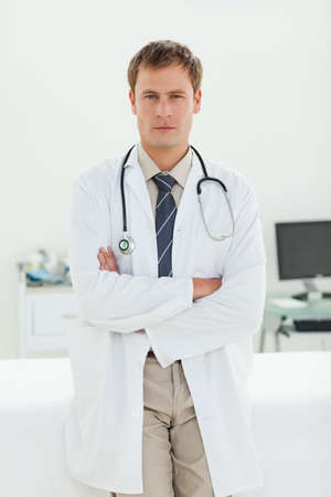 examination room: Serious male doctor with arms folded standing in his examination room LANG_EVOIMAGES