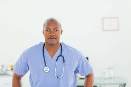 examination room: Male doctor in scrubs standing in examination room LANG_EVOIMAGES