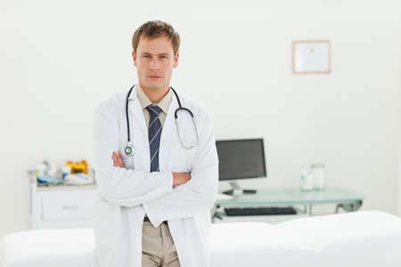 examination room: Male doctor standing in his examination room with his arms folded