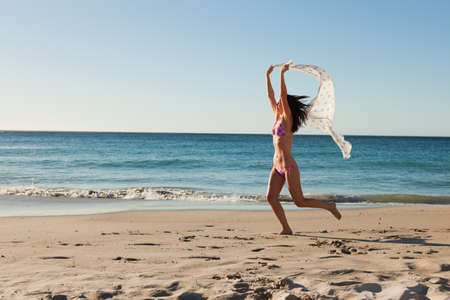 sarong: Attractive woman in bikini running with a sarong on the beach in front of the sea