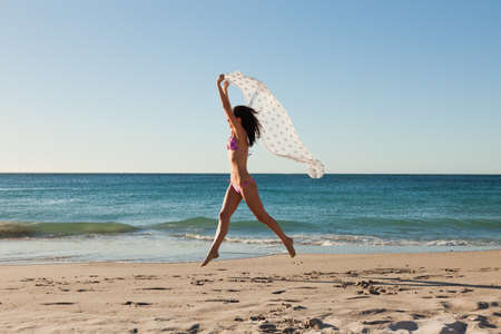 sarong: Attractive woman in bikini jumping with a sarong on the beach in front of the sea