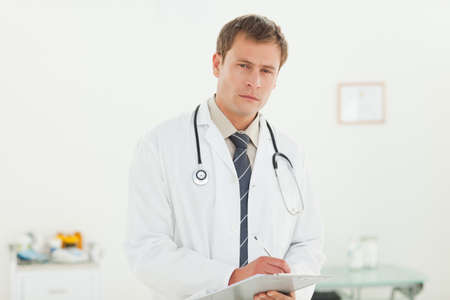 examination room: Young doctor with notepad in his examination room