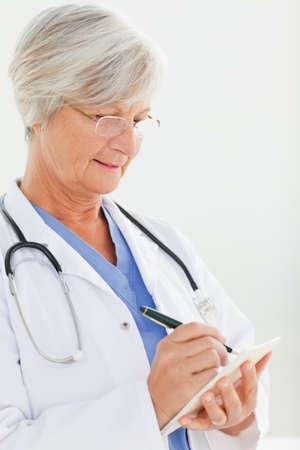 prescription pad: Close up of mature doctor filling in prescription