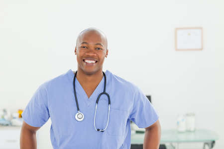 examination room: Smiling male doctor in scrubs standing in examination room