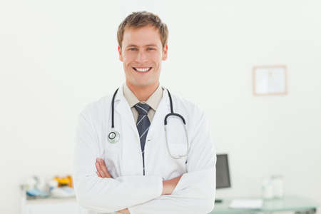 examination room: Smiling young doctor with arms crossed in his examination room