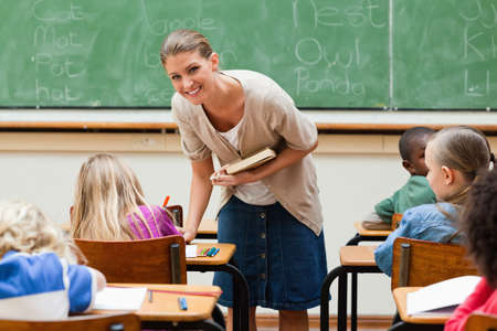 pupils: Smiling elementary teacher next to pupils desk