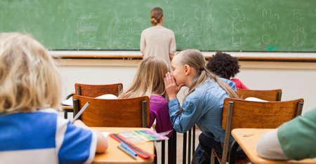 whispering: Little schoolgirl whispering into schoolfellows ears