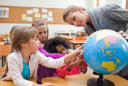 explaining: Elementary teacher explaining globe to her students LANG_EVOIMAGES