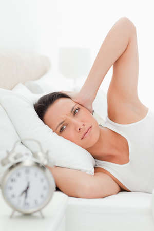 hands over ears: Woman hands over ears in her bed with alarm clock in foreground