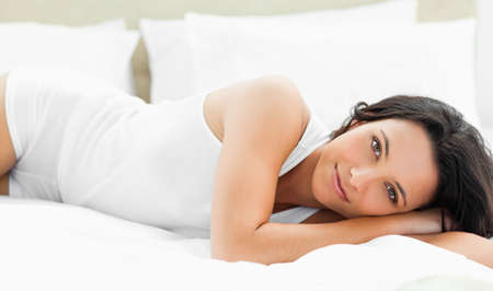 wellness sleepy: Pleasant woman lying on her bed with white sheets
