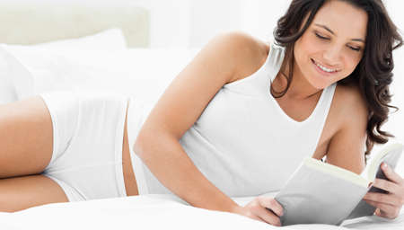 caucasian white: Pretty woman reading a book on her bed with white sheets
