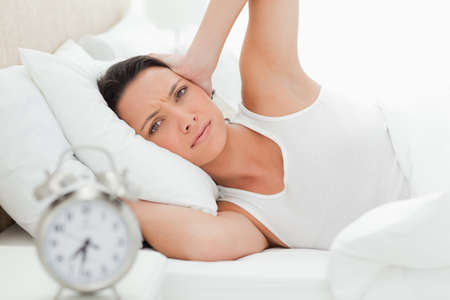 hands over ears: Beautiful woman with hands over ears in her bed with alarm clock in foreground