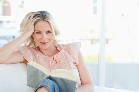 sittting: Smiling female lying on a sofa while reading a book in a bright living room