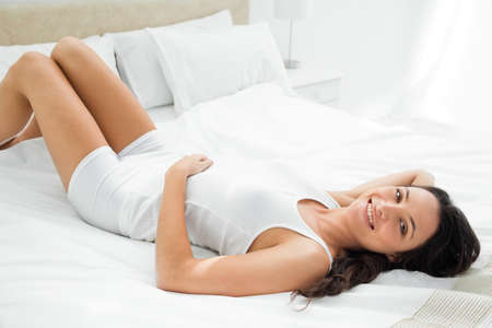 pleasing: Pleasing woman dressed in white lying on her white bed