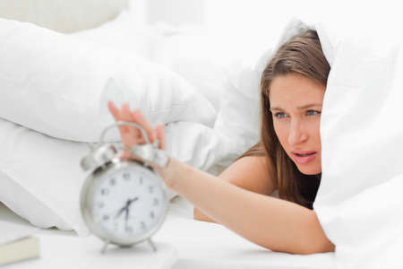 beside table: Sleepy woman turning off her alarm on the beside table