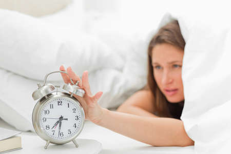 beside table: Woman in her bed turning off her alarm on the beside table