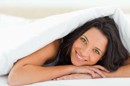 duvet: Woman with green eyes smiling under the duvet
