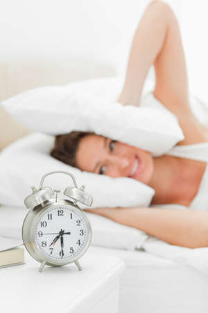 oversleep: Alarms clock is ringing loudly while a woman is putting pillows on her ears in background