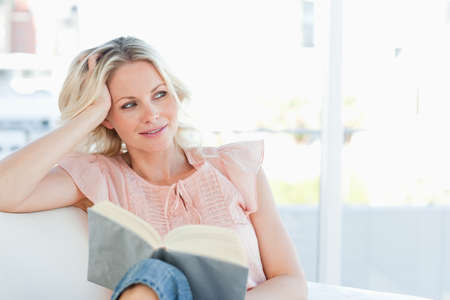 sittting: Cute woman lying on a sofa with a book in a bright living room