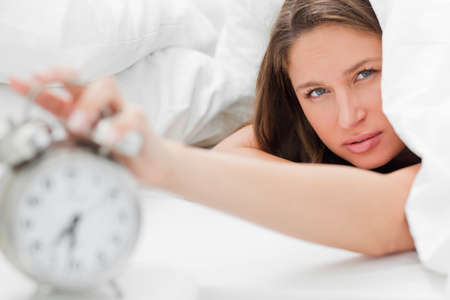 beside table: Sleepy woman is turning off her alarm on the beside table LANG_EVOIMAGES