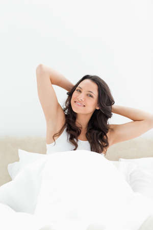 get tired: Smiling brunette waking up in her bed against white background
