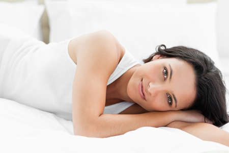 wellness sleepy: Pretty woman lying on her bed with white sheets