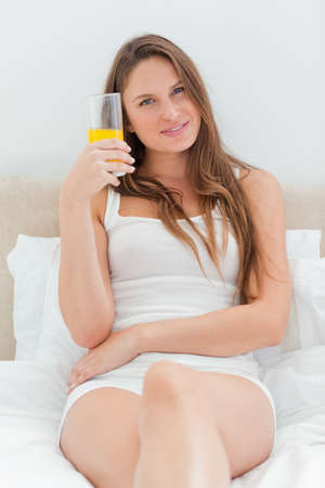 glass bed: Beautiful woman with a glass of juice on her white bed LANG_EVOIMAGES