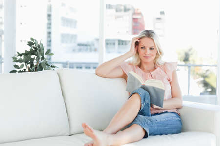 middleaged: Female lying on a sofa while reading a book in a bright living room