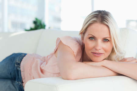 bright eyed: Blue eyed woman lying on her sofa in a bright living room